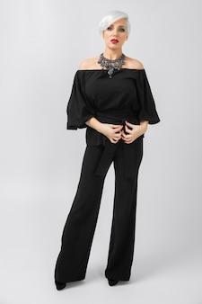 Empresária de moda confiante bonita adulta em roupas folgadas, possing na camiseta cinza