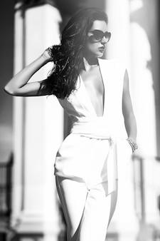 Empresária de moda vestindo terno branco e óculos de sol na rua