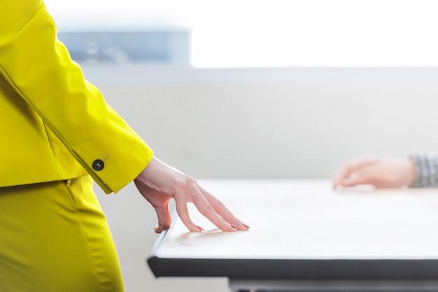 Empresária de pé com as mãos na mesa