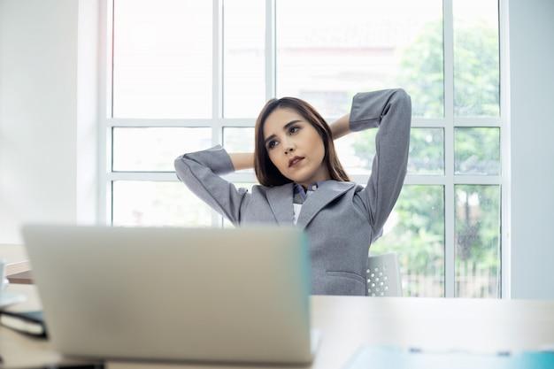 Empresária de pensamento relaxante na confortável cadeira de escritório mãos atrás da cabeça