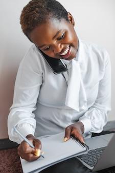 Empresária de plantão escrevendo detalhes de negócios de conceito de negócios telefone celular usando o telefone