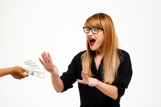 Empresária de sucesso surpresa alcançando dinheiro sobre parede branca