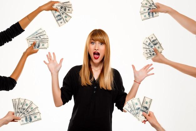 Empresária de sucesso surpresa entre dinheiro sobre parede branca