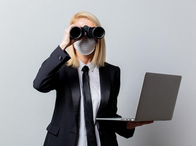 Empresária de terno preto e máscara facial com binóculos e computador