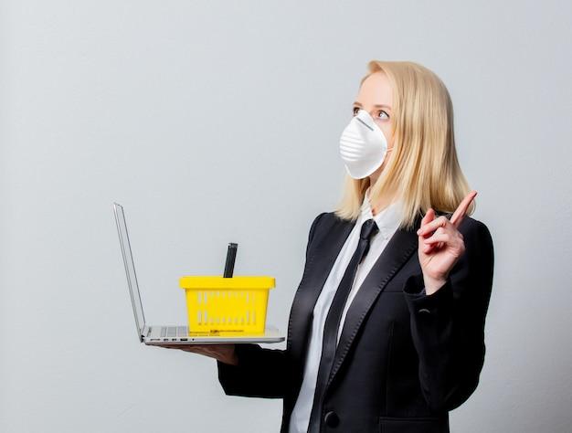 Empresária de terno preto e máscara facial com cesto e computador