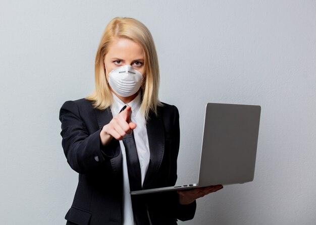 Empresária de terno preto e máscara facial com computador