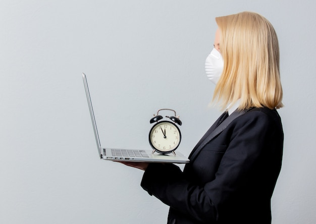 Empresária de terno preto e máscara facial com despertador e computador