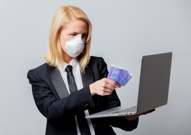 Empresária de terno preto e máscara facial com dinheiro e computador
