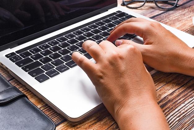 Empresária de vista superior digitando no laptop no local de trabalho. mulher que trabalha no teclado de mão de escritório em casa. conceito de local de trabalho