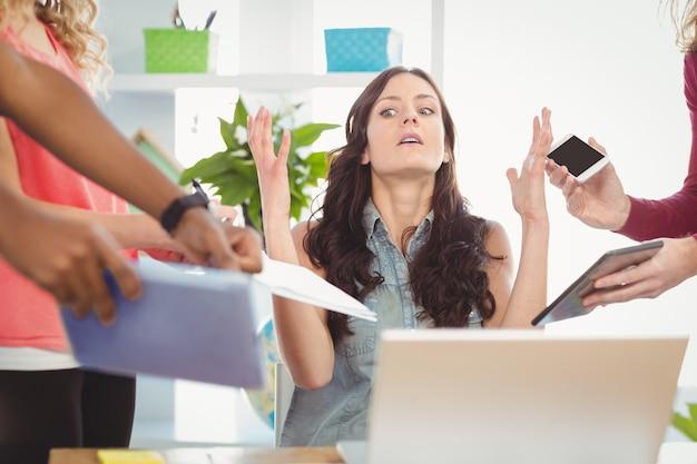 Empresária deprimida gesticulando enquanto está sentado na mesa