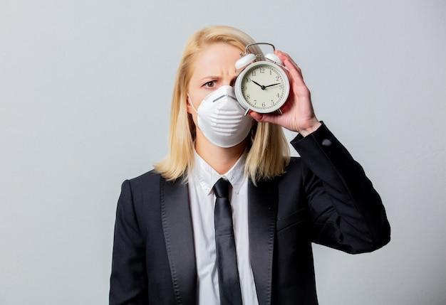 Empresária desesperada em terno preto e máscara facial detém despertador