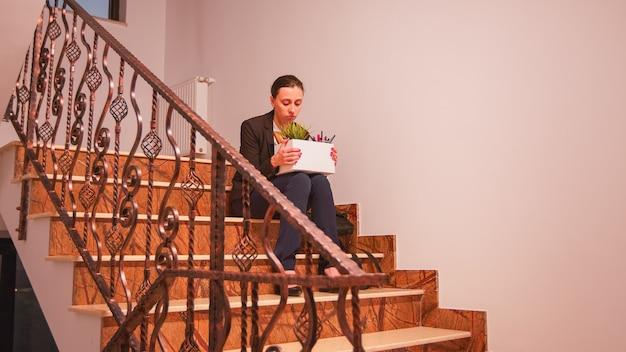 Empresária despedida, sentado na escada em uma empresa de finanças corporativas, chorando, segurando a caixa de coisas pessoais do funcionário corporativo. empresários profissionais de sucesso trabalhando em um edifício financeiro moderno.