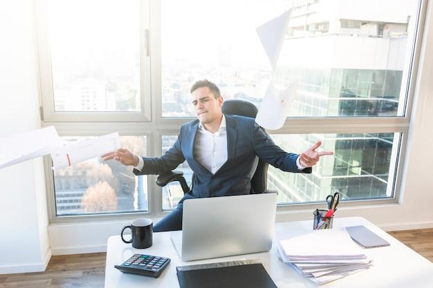 Empresária despreocupada jogando documentos no escritório