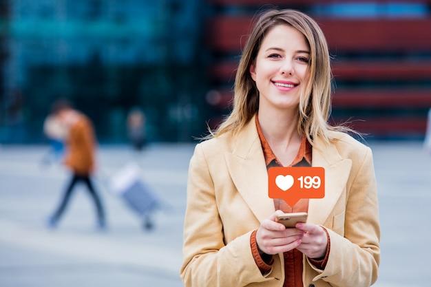 Empresária digitando mensagem por telefone na praça da cidade