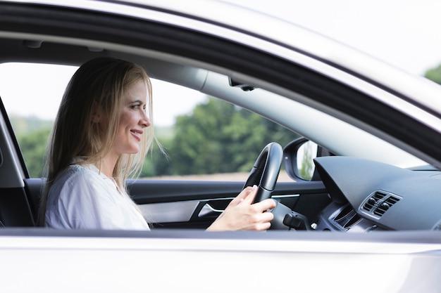 Empresária dirigindo carro cuidadosamente tiro médio