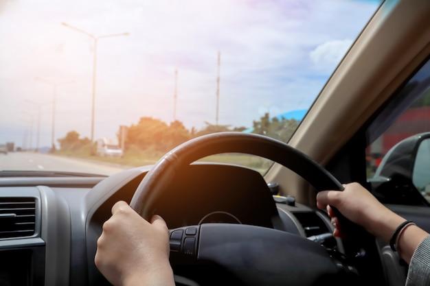 Empresária, dirigindo o carro.
