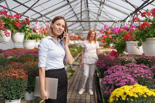 Empresária discutindo ao telefone uma proposta. ela segura um laptop em uma casa verde com flores.