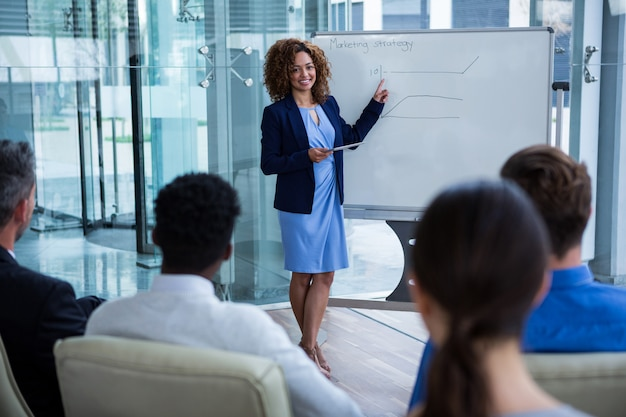 Empresária, discutindo no quadro branco com colegas de trabalho
