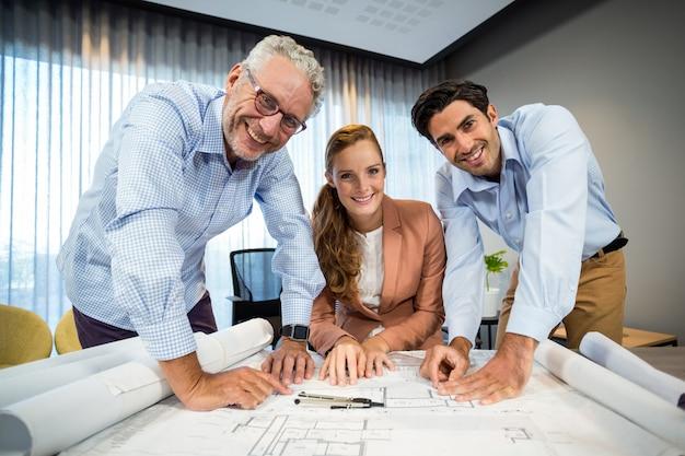 Empresária e colega de trabalho com planta em cima da mesa