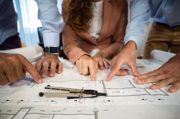 Empresária e colega de trabalho discutindo blueprint na mesa