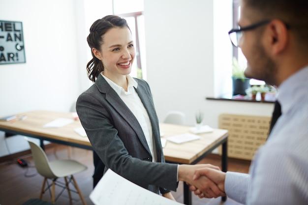 Empresária e empregado, apertando as mãos