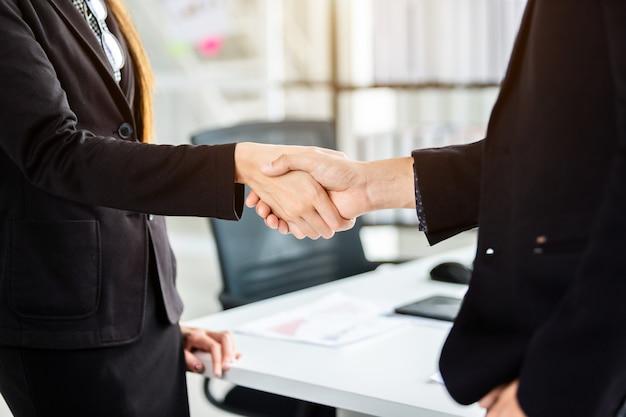 Empresária e empresário apertando as mãos na sala de escritório