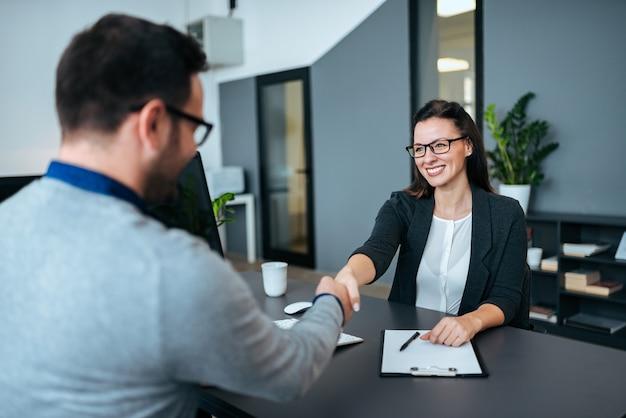 Empresária e empresário apertando as mãos no escritório moderno.