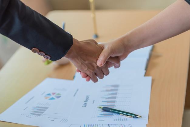 Empresária e empresário apertando as mãos sobre a mesa com papéis no escritório.