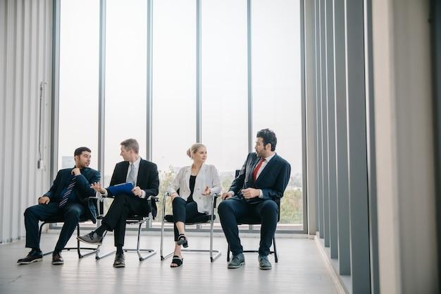 Empresária e empresário estão esperando por uma entrevista de emprego.