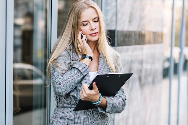 Empresária elegante com prancheta fazendo ligação