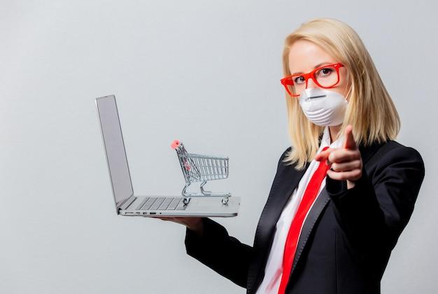 Empresária em máscara facial e óculos vermelhos com carrinho e notebook