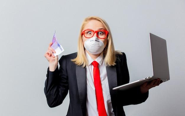 Empresária em máscara facial e óculos vermelhos com dinheiro e notebook