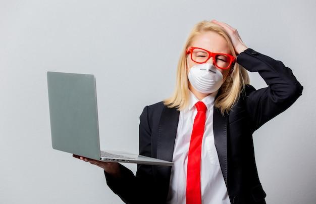 Empresária em máscara facial e óculos vermelhos com notebook
