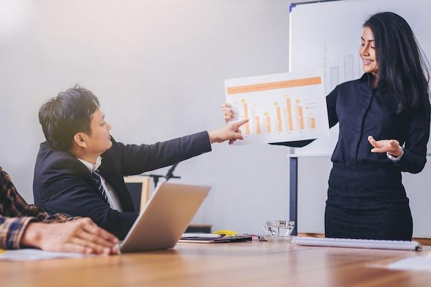 Empresária em pé apresentação e explicar o relatório de negócios para os colegas