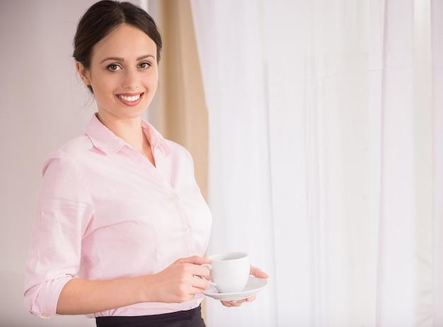 Empresária em pé com uma xícara de café.