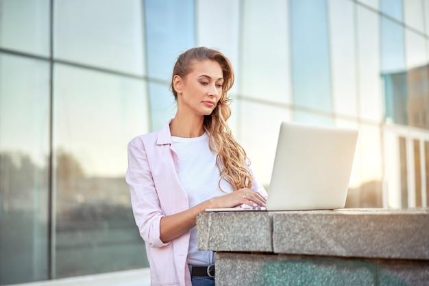 Empresária em pé corporativo construindo dia de verão usando laptop pessoa de negócios trabalhando remotamente