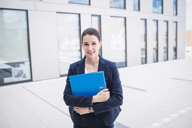 Empresária em pé fora do prédio de escritórios