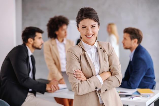 Empresária em pé na sala de reuniões com os braços cruzados