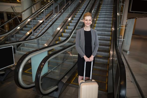 Empresária em pé perto da escada rolante com bagagem