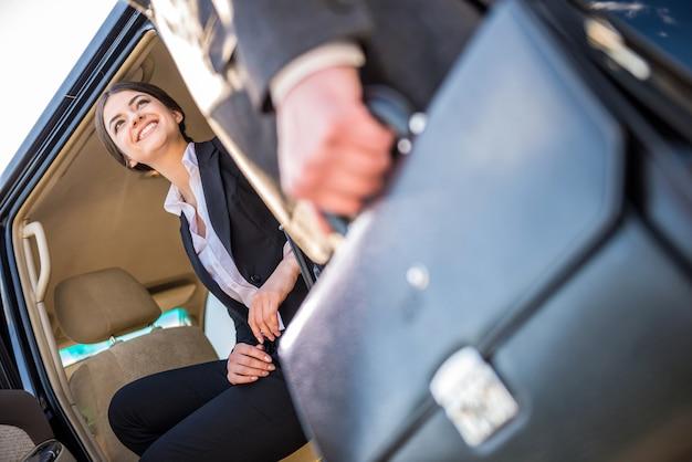 Empresária em terno sentado em seu carro de luxo.