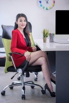 Empresária, em, terno vermelho, sorrindo, e, sentando, em, escritório