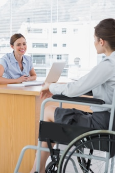 Empresária entrevistando candidato a emprego com deficiência