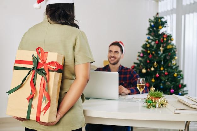 Empresária escondendo um grande presente de natal decorado para uma colega nas costas