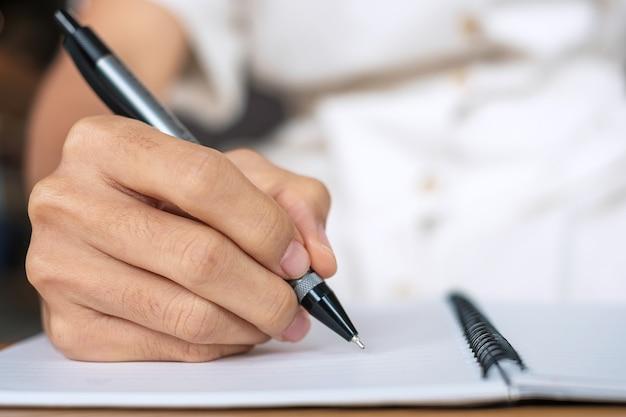Empresária, escrevendo algo no caderno no escritório ou café, mão de mulher segurando a caneta com a assinatura no relatório de papel. conceitos de negócios