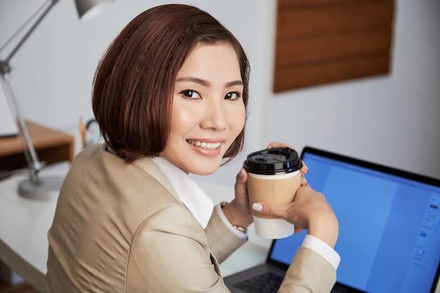 Empresária étnica sorridente com café