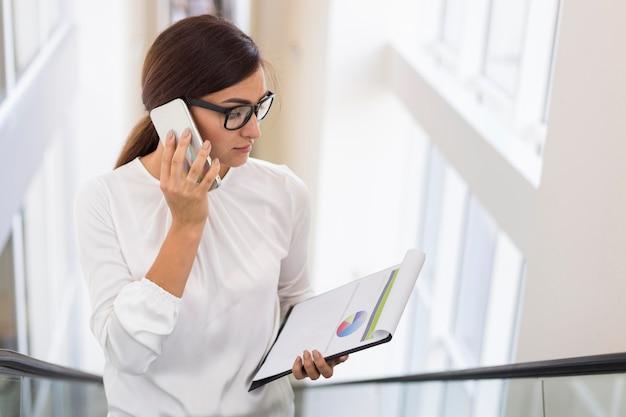 Empresária falando ao telefone enquanto está em uma escada rolante