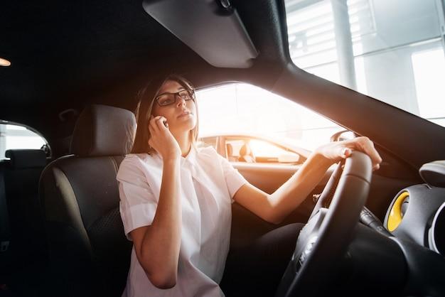 Empresária, falando ao telefone no carro