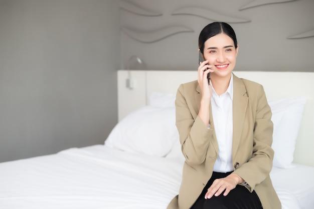 Empresária falando ao telefone no quarto
