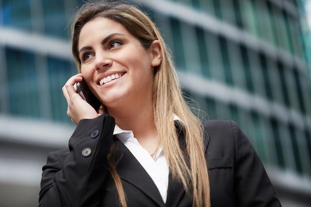 Empresária falando com celular em ambiente urbano