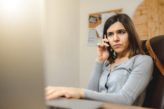 Empresária falando no telefone enquanto digita no teclado do laptop.